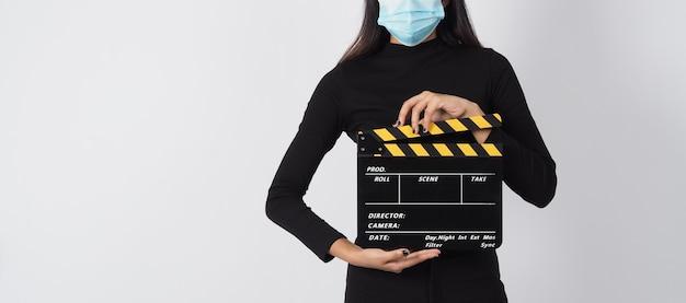 Asiatische frau trägt gesichtsmaske oder medizinische maske und hält schwarzes klappbrett
