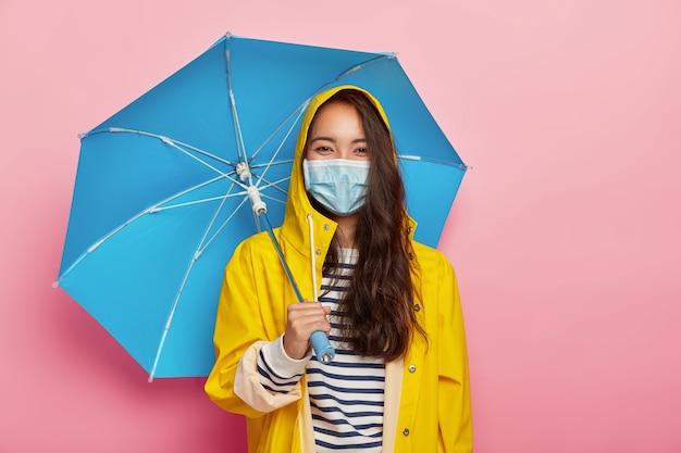 Asiatische frau trägt schutzmaske, sieht sich luftverschmutzung während des regnerischen tages gegenüber, steht unter regenschirm, gekleidet im gelben regenmantel