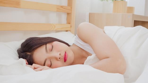 Asiatische frau träumt beim schlafen auf dem bett im schlafzimmer