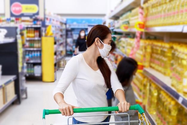 Asiatische frau tragen gesichtsmaske push-einkaufswagen in suppermarket kaufhaus.