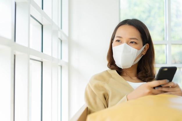 Asiatische frau tragen gesichtsmaske und sitzen im wohnzimmer mit blick nach draußen fenster