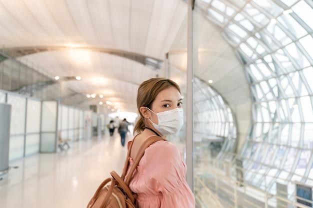 Asiatische frau tragen masken, während sie am flughafenterminal reisen. neues normales konzept zur vorbeugung von covid19-krankheiten.