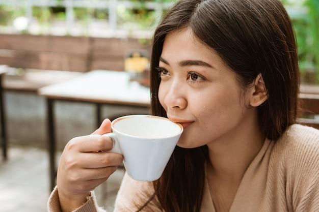 Asiatische frau trinken im café