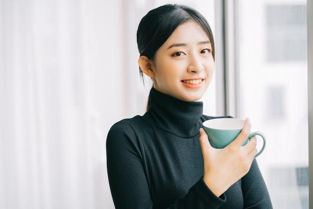 Asiatische frau trinkt kaffee am fenster während der pause