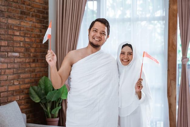 Asiatische frau und ehemann halten nationalflagge des indonesischen