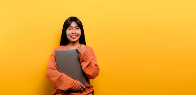 Asiatische frau und laptop und arbeiten gerne foto einer schönen asiatischen frau, die gerne zu hause arbeitet. mit einem laptop-computer gelbes studio arbeiten zu hause konzept