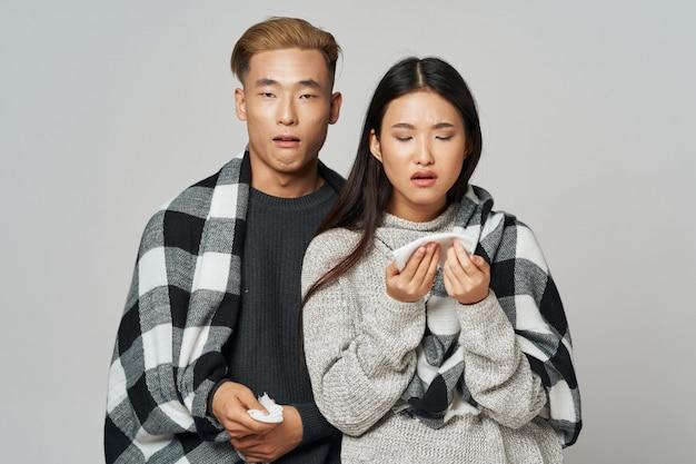 Asiatische frau und mann auf hellem farbhintergrund, der modell zusammen aufwirft