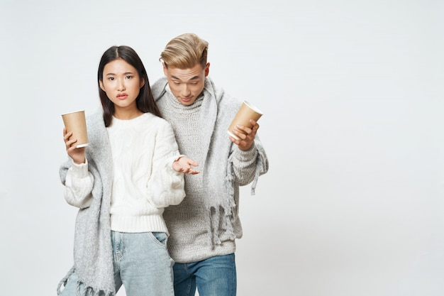 Asiatische frau und mann auf hellem farbhintergrund, der modell zusammen wirft