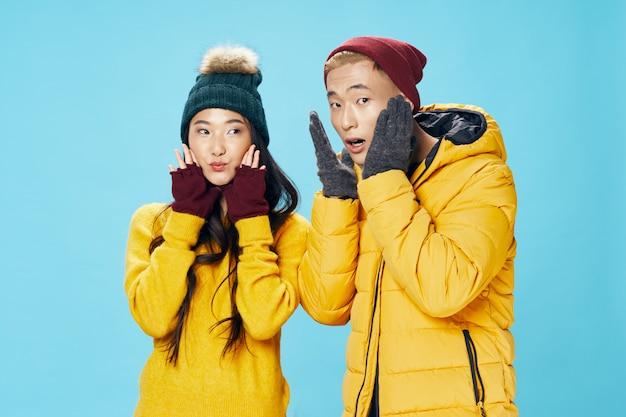 Asiatische frau und mann, die mit winterkleidung aufwerfen