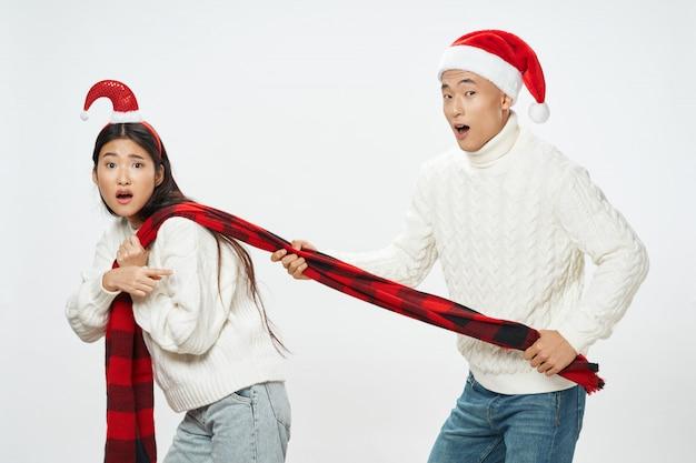 Asiatische frau und mann mit weihnachtsmützen, die zusammen aufwerfen