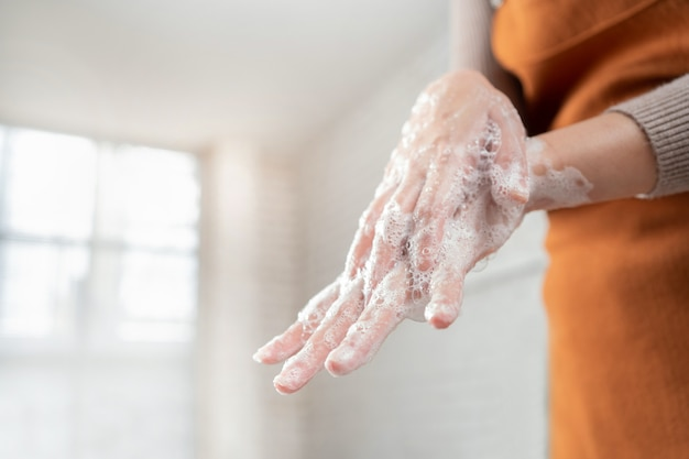Asiatische frau verwenden seife, um ihre hände im badezimmer zu waschen, um das virus loszuwerden.