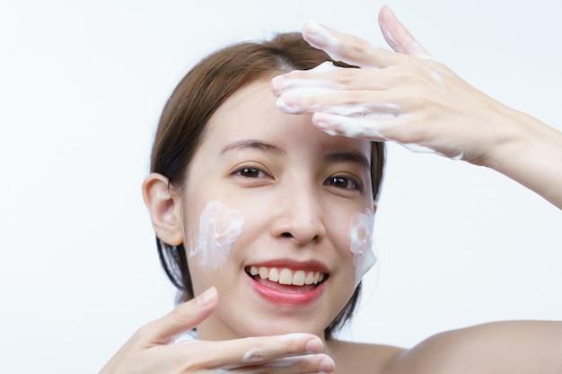 Asiatische frau waschen ihr gesicht mit blasenreinigungsschaum lokalisiert auf weiß.