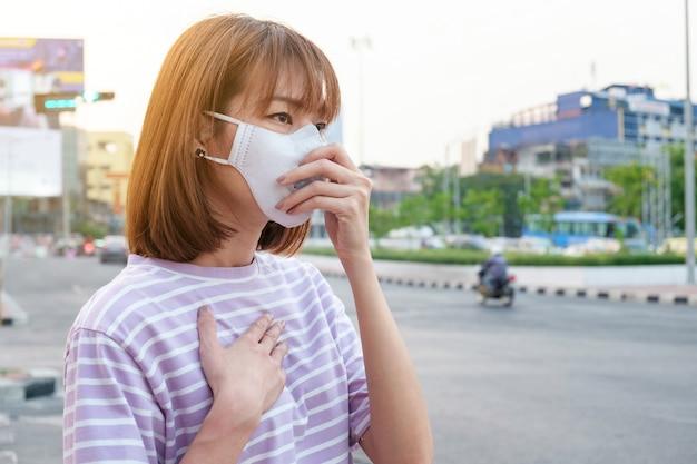 Asiatische frau, welche die n95 atemschutzmaske gegen luftverschmutzung an der straße und am verkehr in bangkok trägt