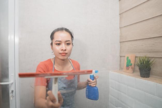 Asiatische frau wischt mit einem scheibenwischer und hält ein flaschensprühgerät beim reinigen des toilettenglases im badezimmer