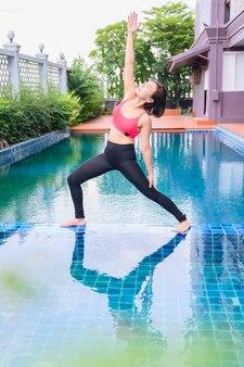 Asiatische frau yoga-atmung und meditation allein im schwimmbad zu hause. bewegung und training im freien für gesundheit und wohlbefinden.