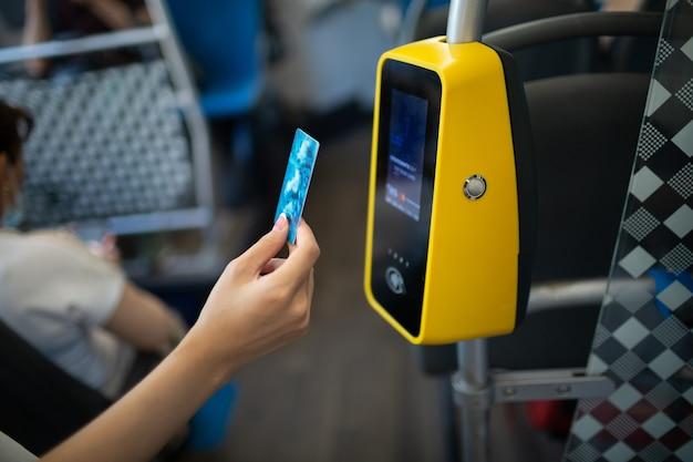 Asiatische frau zahlt kontaktlos mit plastikkarte für die öffentlichen verkehrsmittel im bus