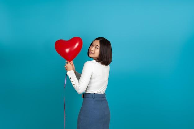 Asiatische frau zurück und hält einen roten ballon in zwei händen