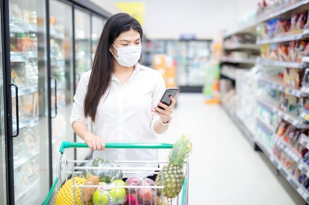 Asiatische fraucheckliste durch smartphone und einkaufen mit maske, die sicher für lebensmittel kauft, sicherheitsmaßnahmen im supermarkt.