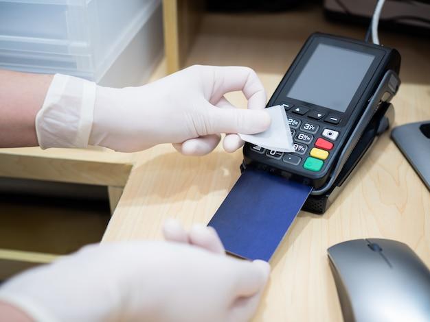 Asiatische frauen an der kasse verwenden alkoholtupfer, um kreditkartenterminals oder automaten zu reinigen, bevor sie die kundenkarte einlösen, um die ausbreitung des coronavirus zu verhindern. covid-19, coronavirus, soziales distanzkonzept.