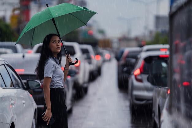 Asiatische frauen benutzen einen regenschirm, der während des regens über die straße läuft
