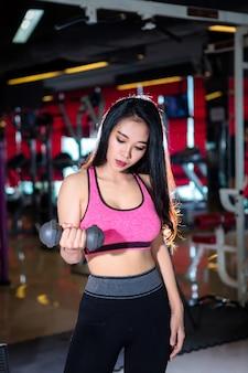 Asiatische frauen der eignung, die übungen tuend mit dummkopfsport im sportgymnastikinnenraum durchführen