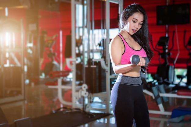 Asiatische frauen der eignung, die übungen tuend mit dummkopfsport im turnhallen-backgr durchführen
