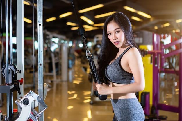 Asiatische frauen der eignung, die übungen tuend mit rudermaschine in der sportgymnastik durchführen