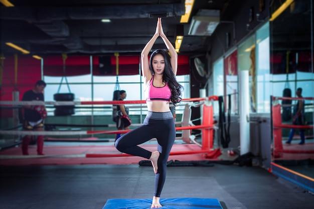 Asiatische frauen der eignung, die yogatraining im sportgymnastikinnenraum und im fitnessstudio ausüben