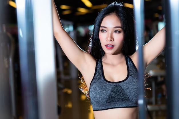 Asiatische frauen der eignung, welche die übungen ausübt, die die schulter- und kastenmuskeln im sportgymnastikinnenraum und im fitnessstudio trainieren