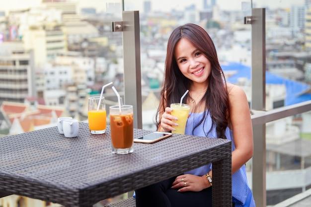 Asiatische frauen des porträts, die in einem restaurant mit einem glas pina colada in der hand und im orangensaft sitzen