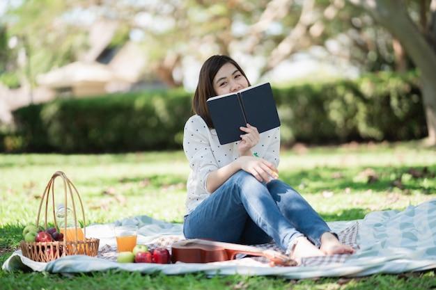 Asiatische frauen, die auf dem gras während eines picknicks sitzen und lied in einem park schreiben