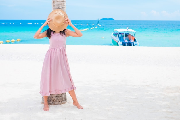 Asiatische frauen, die auf meeresstrand mit rosa kleid stehen, freuen sich über sommer im freien am sandstrand mit blauem himmel und meer