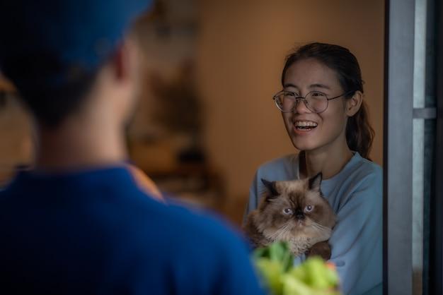 Asiatische frauen, die eine katze im arm halten, stehen vor der tür, um ihren online-lebensmitteleinkauf vom lieferer abzuholen, online-shopping-konzept, lifestyle mit technologie.