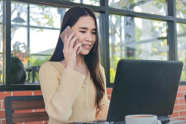 Asiatische frauen, die handy-geschäftsvertrag online-technologie anrufen, arbeiten von zu hause aus