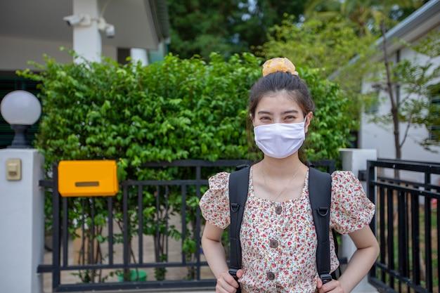 Asiatische frauen, die hinter dem tragen einer schutzmaske im gesicht zum schutz der luftverschmutzung, der partikel und zum schutz des grippevirus, der influenza, des coronavirus in der stadt lächeln