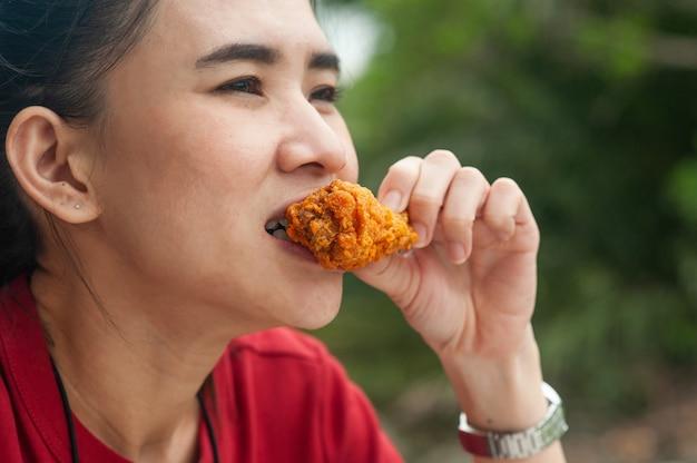 Asiatische frauen, die hühnerflügel essen, der auf tisch sitzt