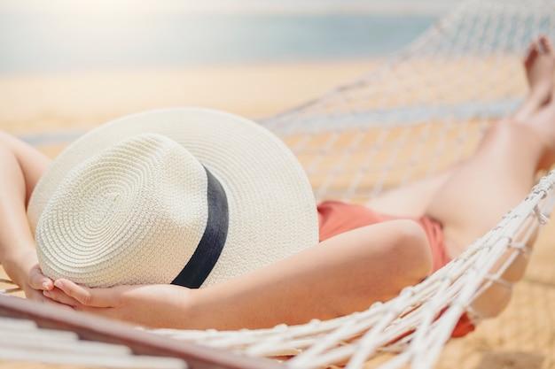 Asiatische frauen, die im hängematten-sommerurlaub am strand entspannen
