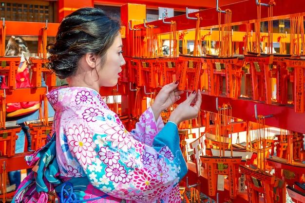 Asiatische frauen, die japanischen traditionellen kimono tragen, der das schöne in fushimi inari-schrein in kyoto, japan besucht