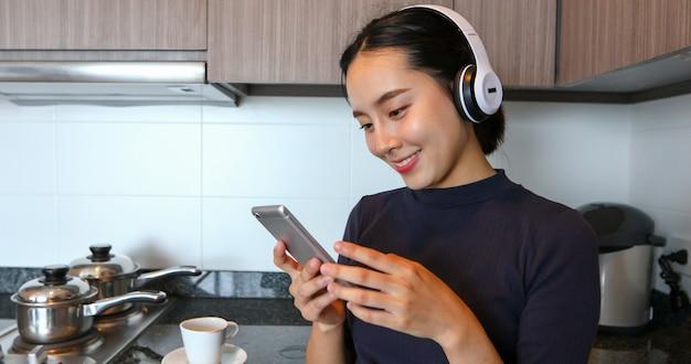 Asiatische frauen, die kopfhörer tragen und musik in der küche zu hause hören