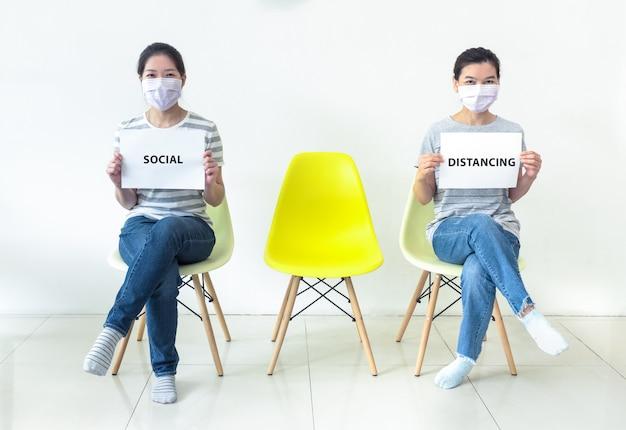 Asiatische frauen, die masken tragen, die zeichen mit text halten soziale distanzierung, um die ausbreitung der coronavirus-infektion während der krise von covid-19 zu verringern. arbeit von zu hause aus und soziales distanzierungskonzept.