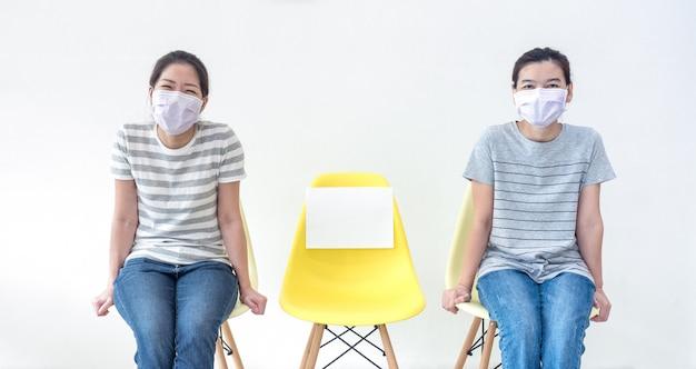 Asiatische frauen, die masken tragen, sitzen auf dem stuhl mit papier oder kopieren platz für text, machen soziale distanz und einen neuen normalen lebensstil während des ausbruchs von covid-19.