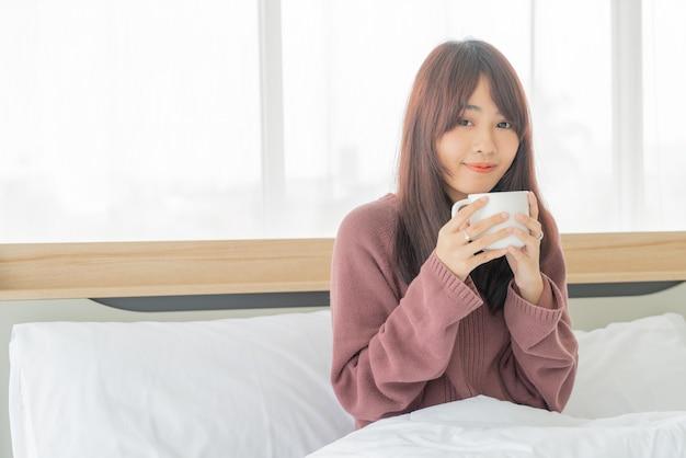 Asiatische frauen, die morgens kaffee auf dem bett trinken