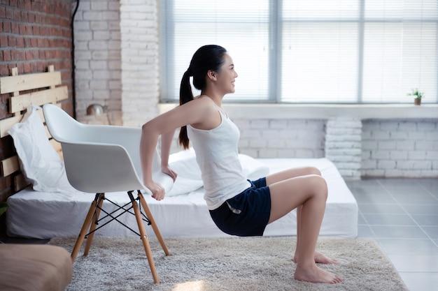 Asiatische frauen, die morgens zu hause trainieren. sie trainiert mit einem stuhl. erhöhen sie die armmuskulatur