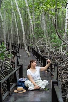 Asiatische frauen, die naturwald reisen und smartphone verwenden. wanderweg im tropischen dschungel.