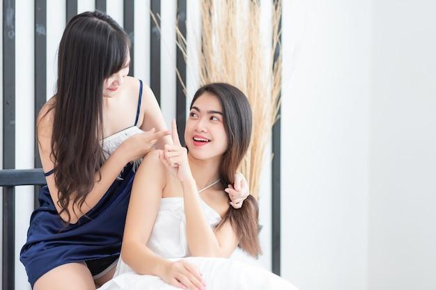Asiatische frauen, die pyjamas tragen und einander ins gesicht und in die augen schauen