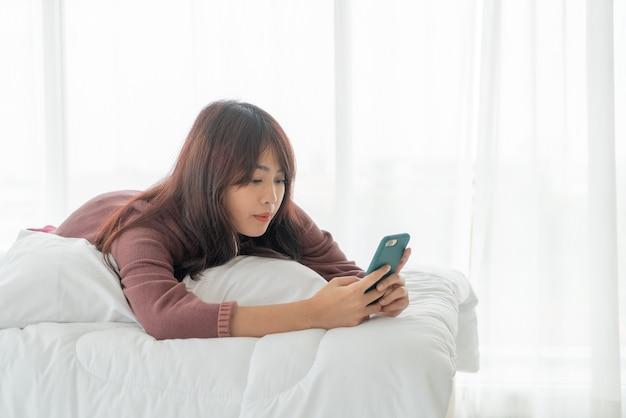 Asiatische frauen, die smartphone auf bett spielen