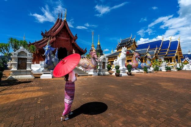 Asiatische frauen, die traditionelle thailändische kleidungskostüme gemäß thailändischer kultur am tempel in chiang mai tragen