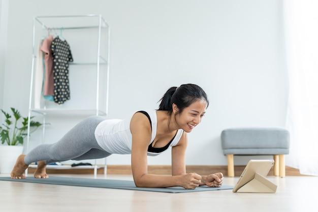 Asiatische frauen, die yogaplanken machen, folgen einem professor in einem video, das in taplet als praxis gezeigt wird. schöne frauen tragen trainingskleidung und trainieren gerne zu hause.