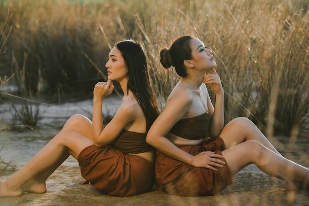 Asiatische frauen drama-stil kleid thailändische tracht tragen. porträt der schönen freundin, die am strand mit grasfeldsonnenuntergangsnatur sitzt