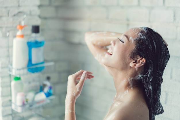 Asiatische frauen duschen im badezimmer, er ist glücklich und entspannt.